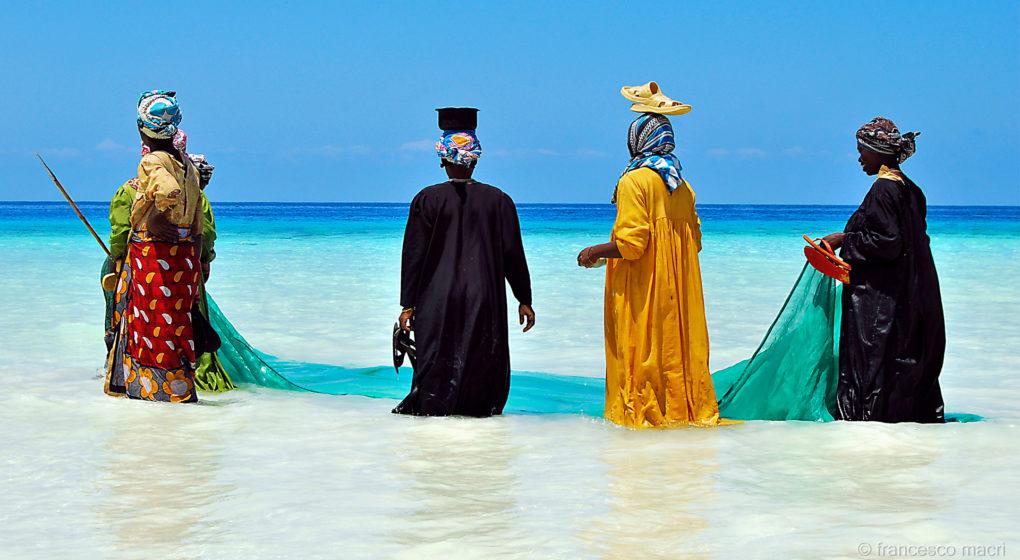 Zanzibar - barevně oblečené ženy kráčí mořem a pokladna miniPOS už funguje i zde
